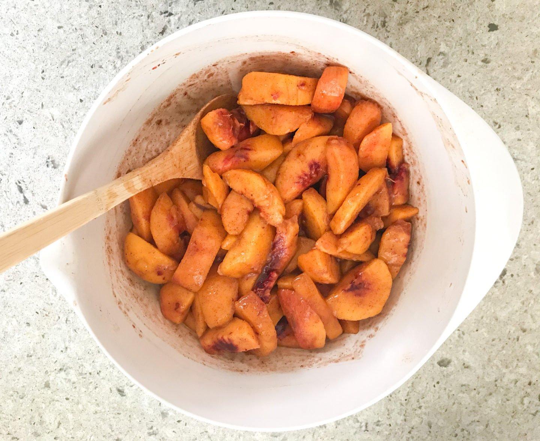 For fresh peach cobbler, combine peaches, white sugar, brown sugar, cinnamon, nutmeg, lemon juice, and cornstarch. Toss to coat evenly.