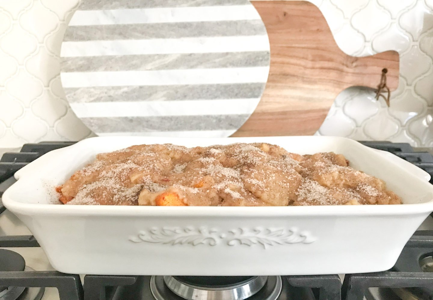 Remove peaches from oven, and drop spoonfuls of the topping over them. Then, sprinkle entire cobbler with the cinnamon and white sugar mixture noted below.