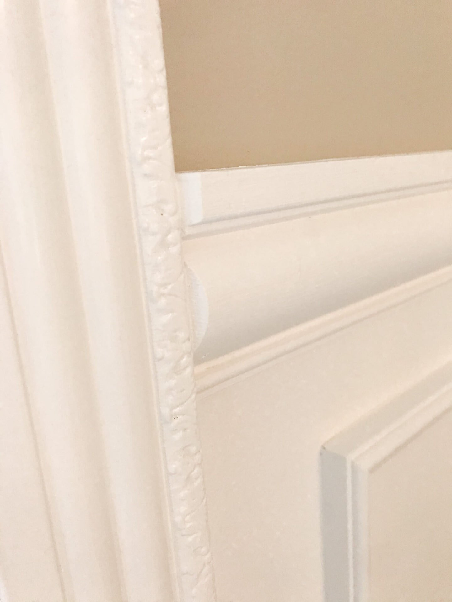 Beveled edge of chair rail installed against the window trim